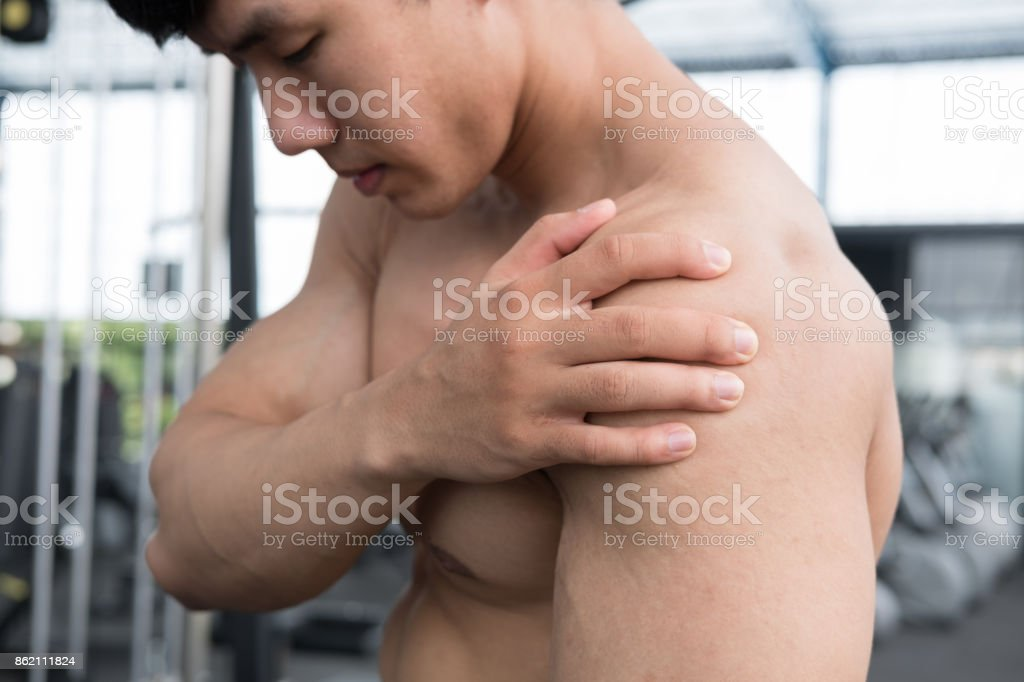 muscular male having pain on shoulder in gym.  young man injure while workout in fitness center. bodybuilder feel hurt while exercise at health club. Sports injury, muscle intense. stock photo