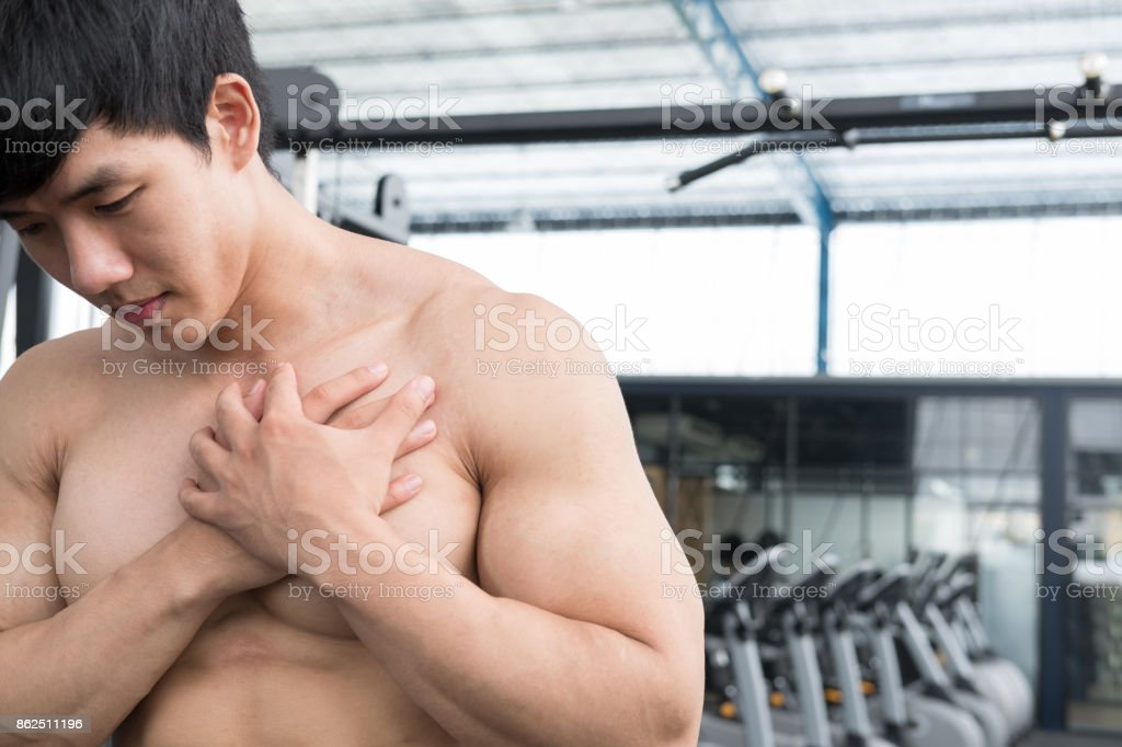 muscular male having pain on shoulder in gym.  young man injure while workout in fitness center. bodybuilder hurt while exercise at health club. Sports injury, muscle intense. stock photo