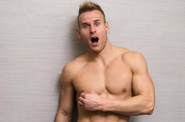 männliche muskeln schmerzen hast, ziehen brustwarzen-piercing mit seiner hand - brustpiercing stock-fotos und bilder