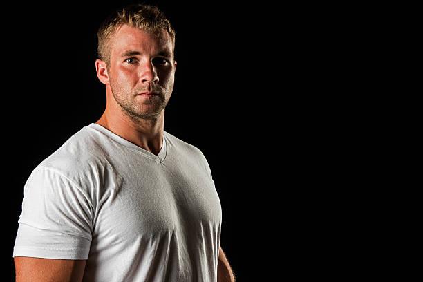 muscular male portrait against black background - macho fotografías e imágenes de stock