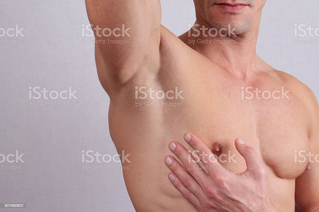 Muscular male torso, chest and armpit hair removal. stock photo