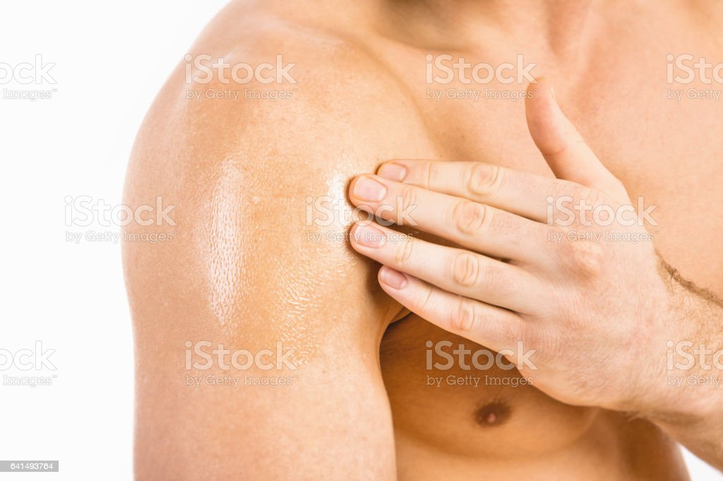 Muscular man applying testosterone gel on shoulder stock photo
