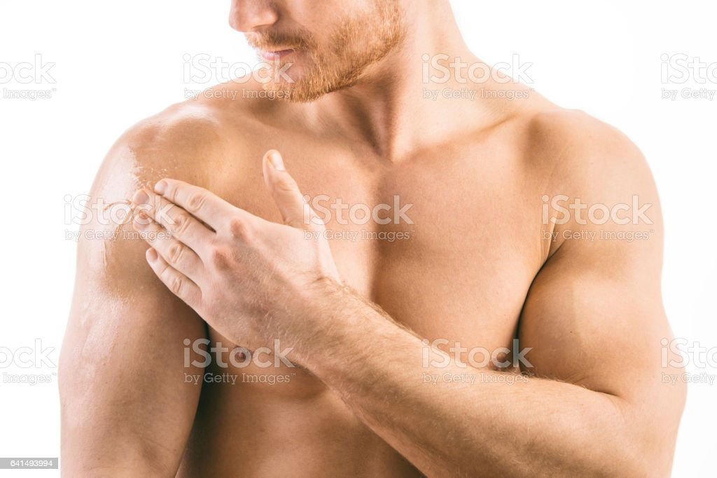 Muscular man applying testosterone gel on shoulder stock photo