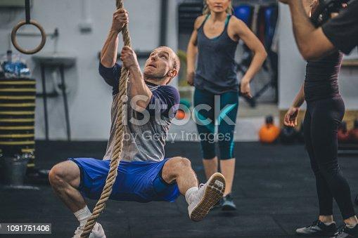 904150892 istock photo Muscular man climbing rope 1091751406