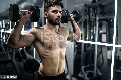 Young and muscular man doing a exercise for biceps