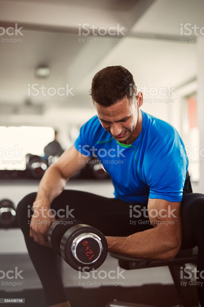 Muscular man doing bicep curls with a dumbbell. stock photo