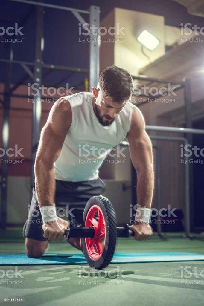 Muscular man doing exercises with abdominal toning wheel in gym stock photo