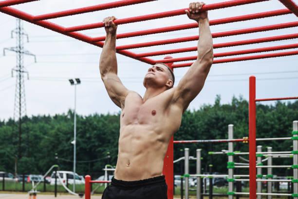 muskulös man gör pull-ups på horisontella bar - utegym vid lekplats bildbanksfoton och bilder