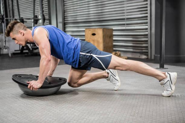 Muscular man doing push up on bosu ball stock photo