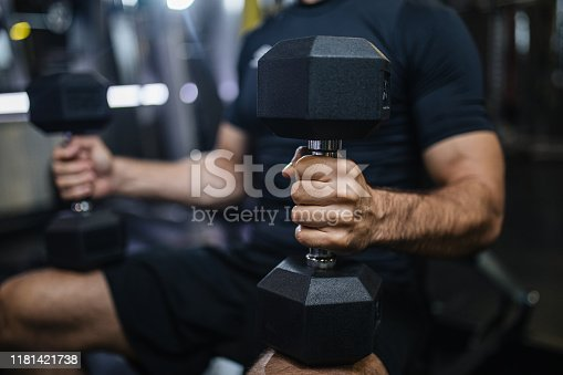 Strong muscular man working out at his gym