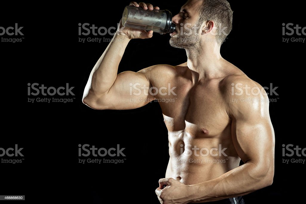 Muscular man drinking a protein shake from a bottle stock photo