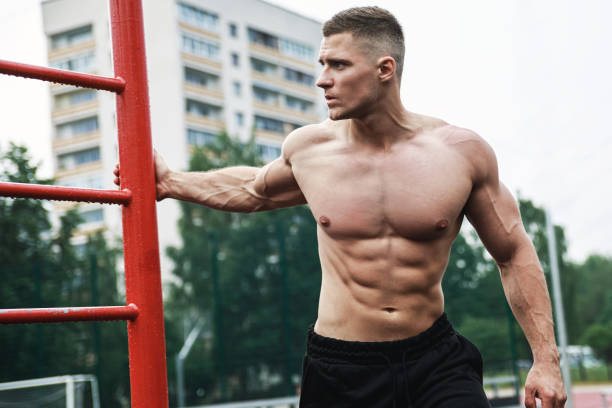 Muscular man during his workout on the street stock photo