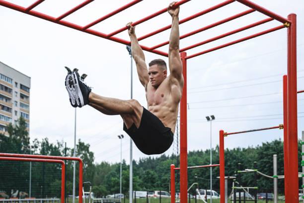 muskulös man under sin träning på gatan - utegym vid lekplats bildbanksfoton och bilder