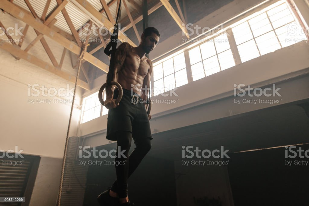 Muscular man exercising on gymnastic rings stock photo