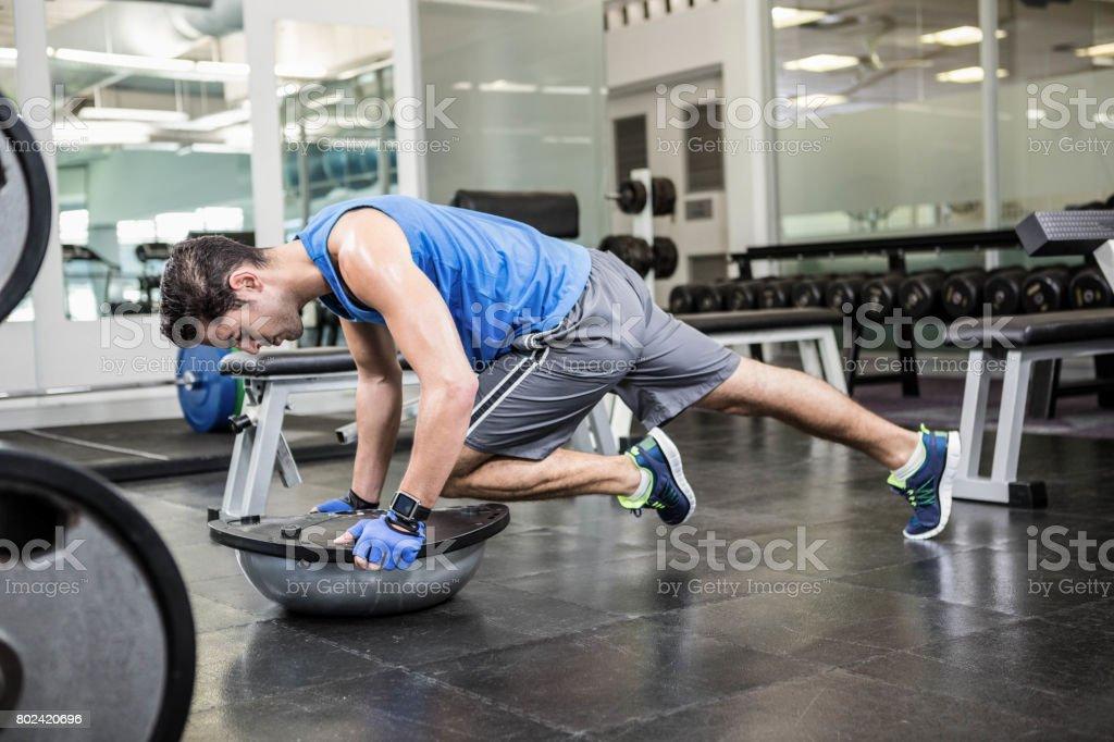 Muscular man exercising with bosu ball stock photo