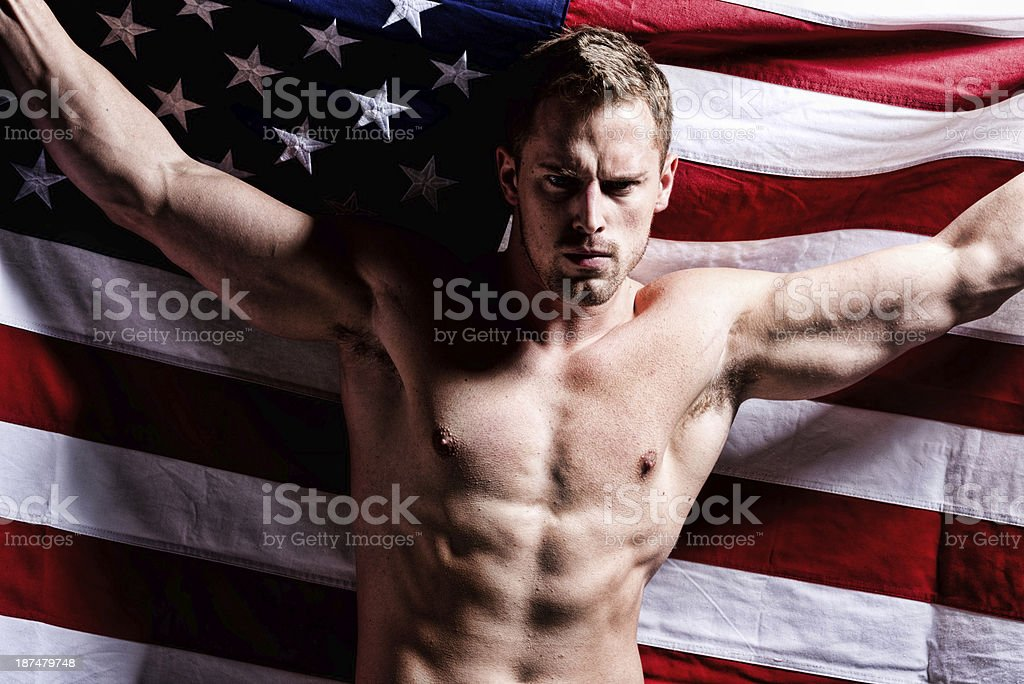 Muscular man holding American flag royalty-free stock photo