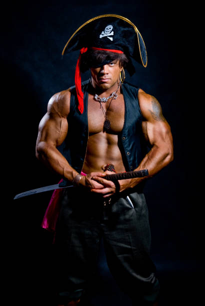 Muscular man in a pirate costume with a sword on a black background stock photo