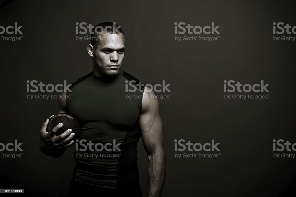 Muscular man in black tank top holding a football stock photo