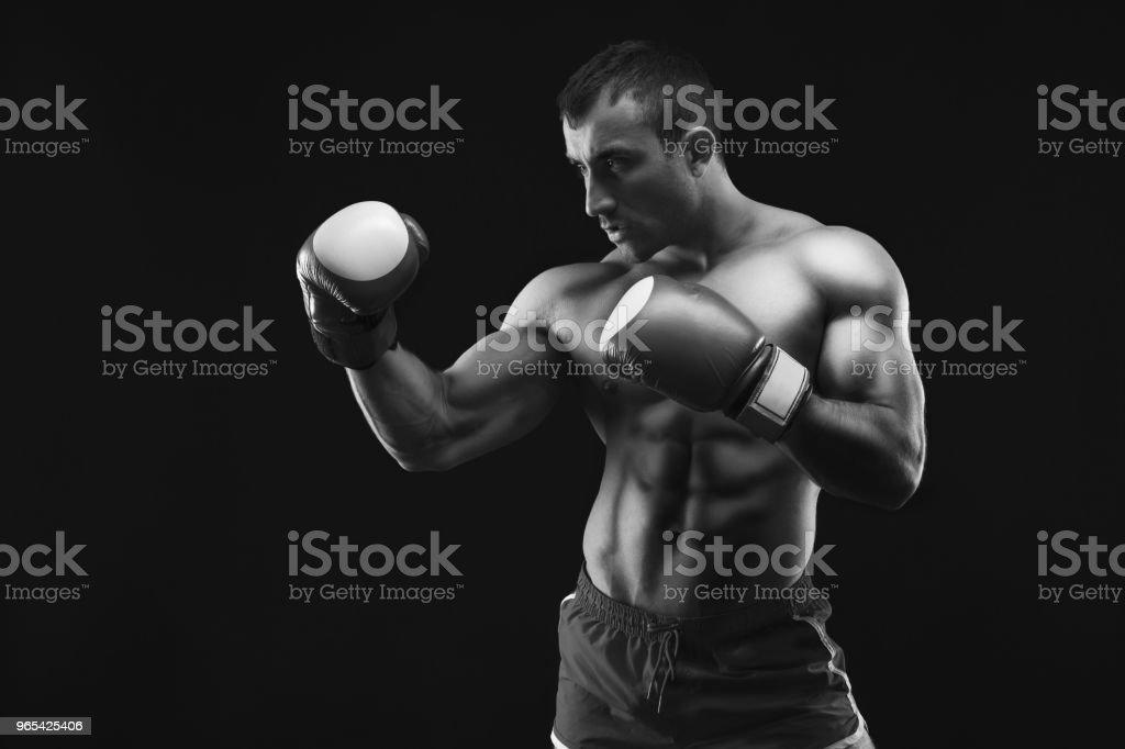Muscular man in boxing gloves at black background zbiór zdjęć royalty-free