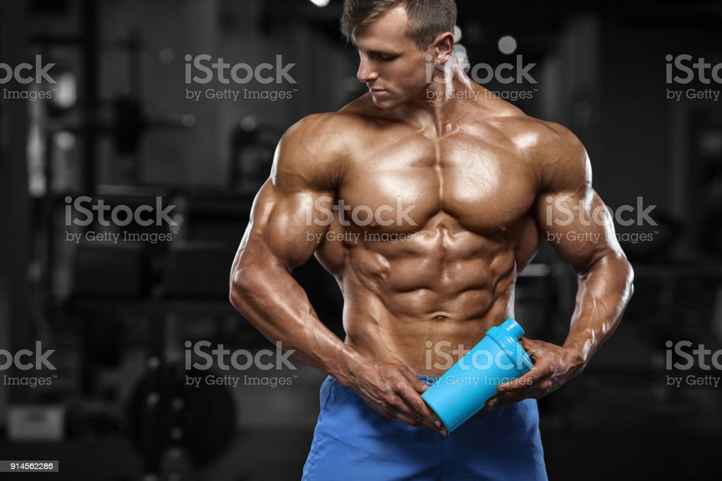 Muscular man working out in gym, doing stomach exercises