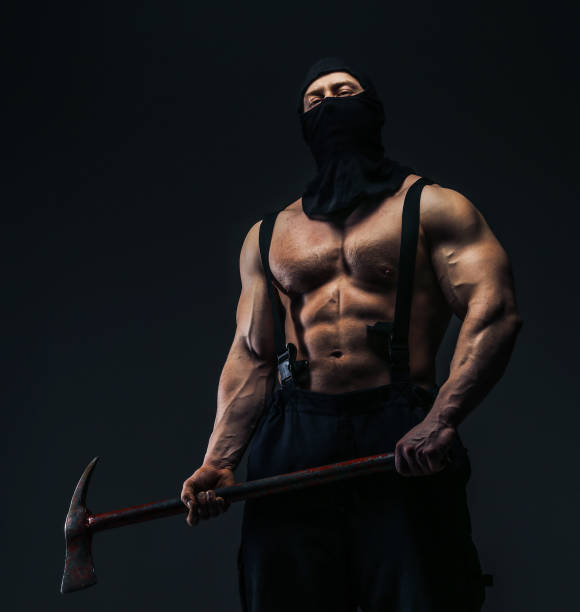 Muscular man in mask holding axe stock photo
