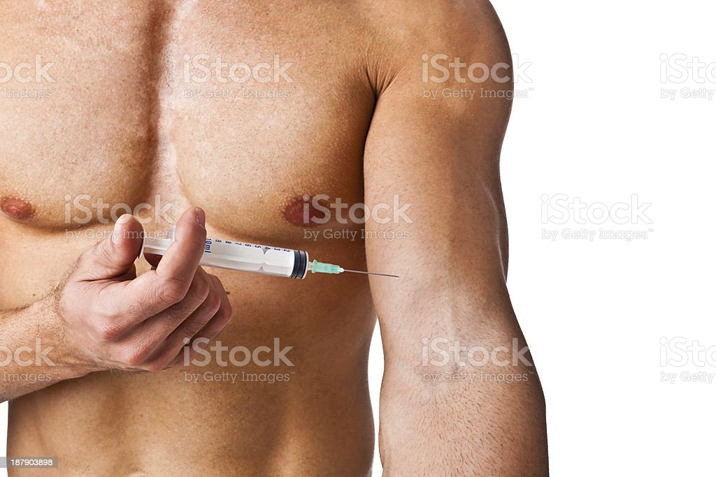 Muscular man injecting a needle into his arm stock photo