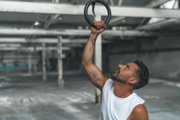 muskulöser mann ist ausübung mit gymnastik ringen - gymnastik tattoo stock-fotos und bilder
