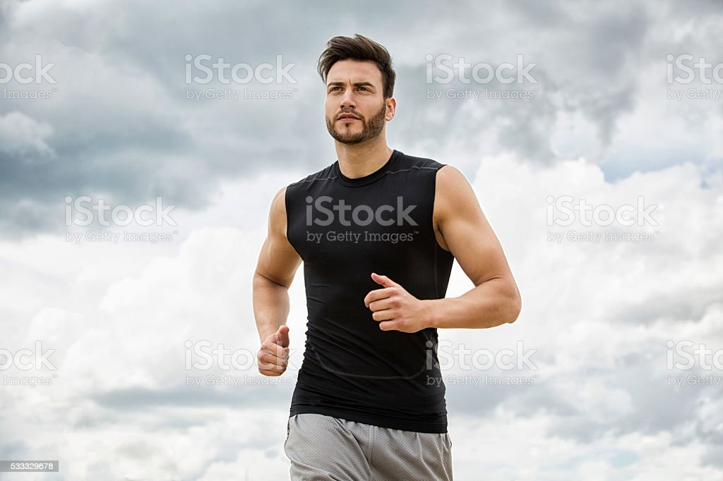 Muscular man jogging outdoors, dramatic sky backdrop stock photo