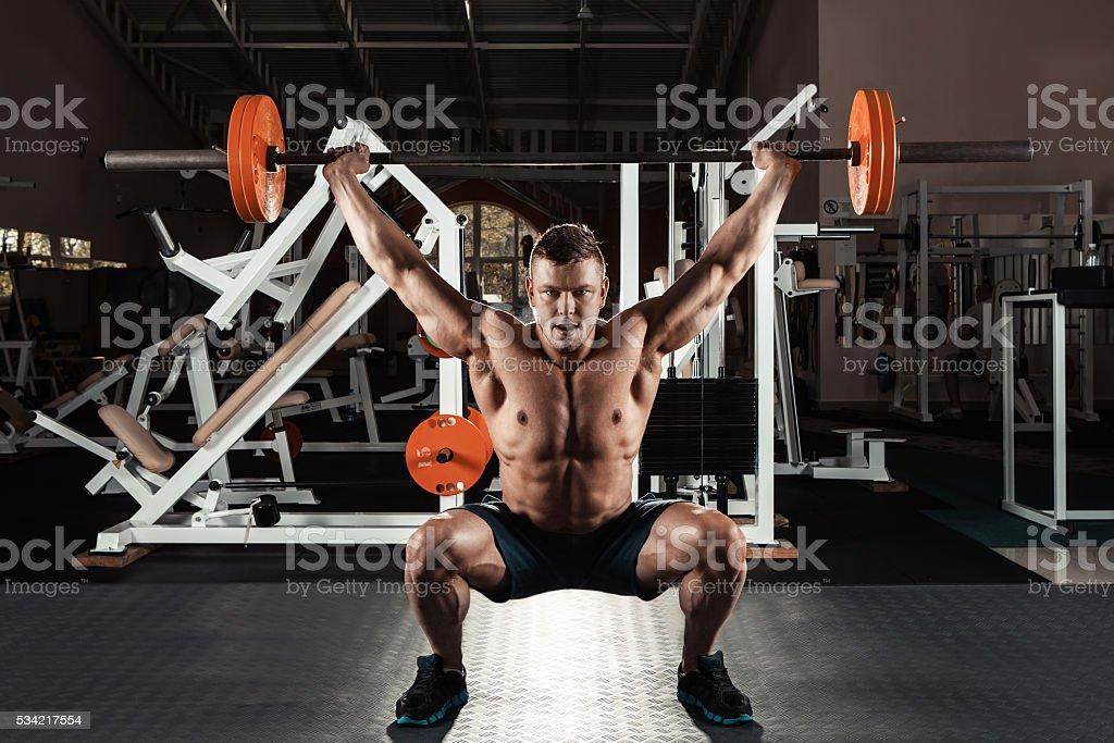 Muscular man  lifting a barbell stock photo