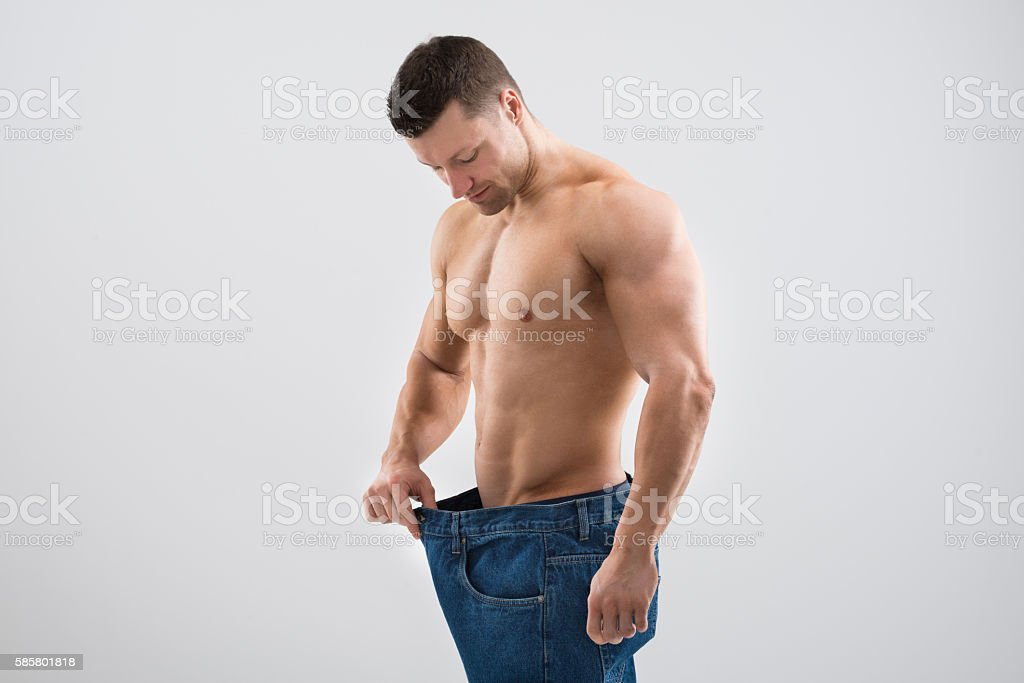 Muscular Man Looking At Weight Loss While Holding Old Jeans stock photo