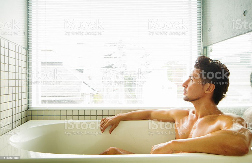 Muscular man looking pensively out of window while bathing stock photo