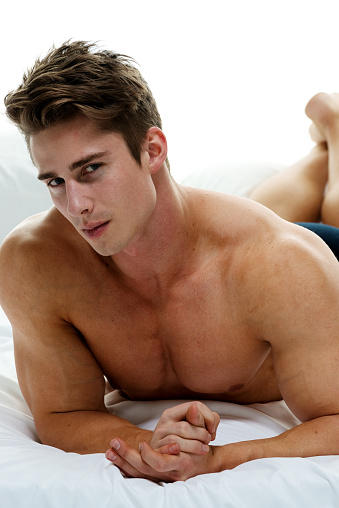 Muscular Man Lying On Bed And Looking At Camera Stock