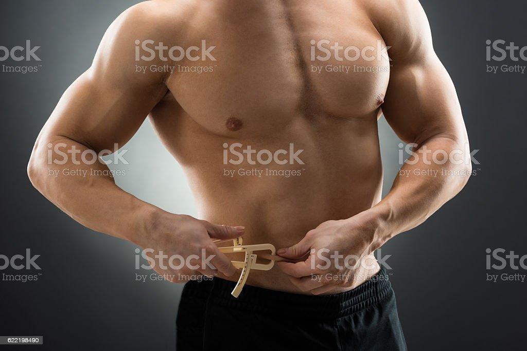 Muscular Man Measuring Fats With Caliper - foto de acervo