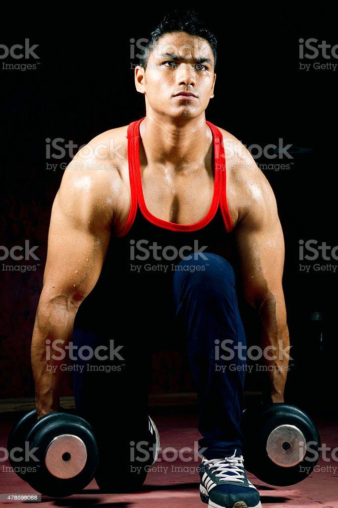 Muscular man picking up dumbbells stock photo