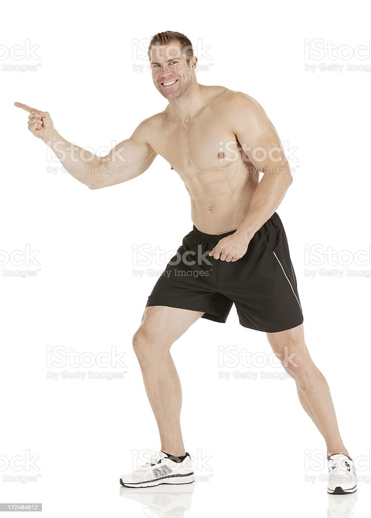 Muscular man pointing sideways and smiling royalty-free stock photo