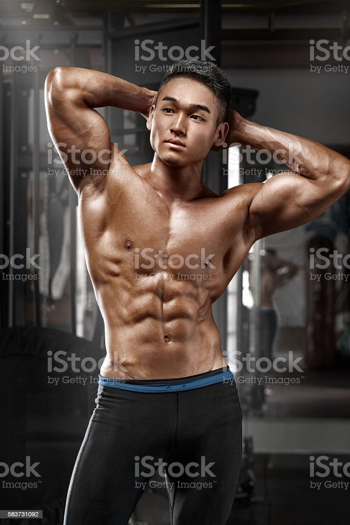 Muscular man posing in gym, shaped abdominal, working out stock photo