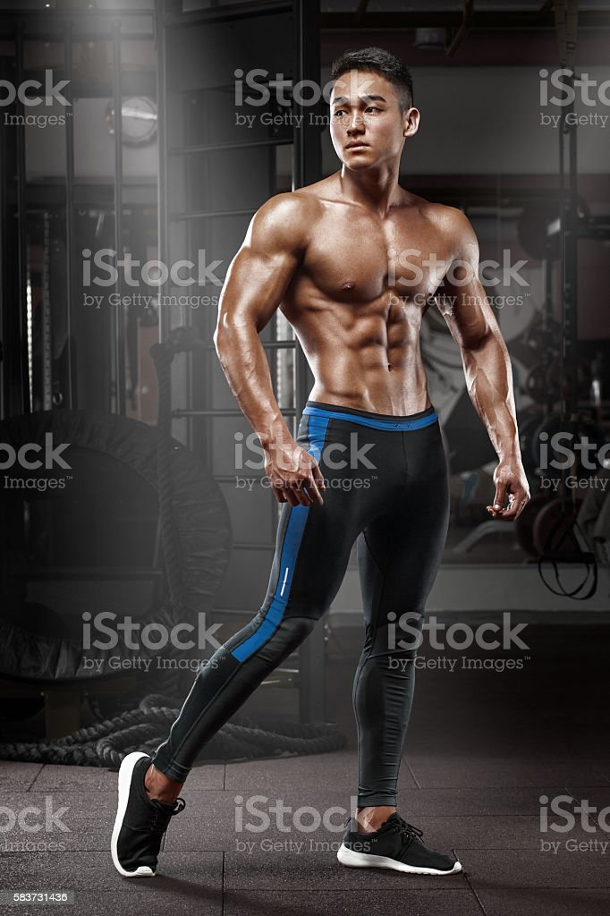 Muscular man posing in gym, torso abs, working out stock photo