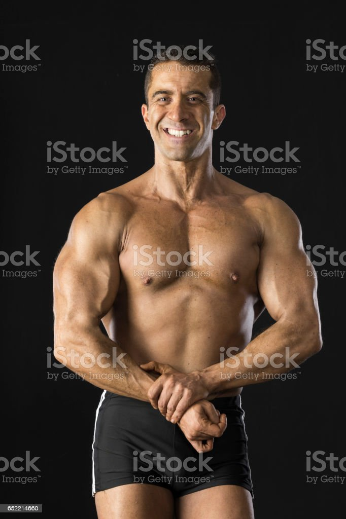 Muscular man posing in the studio front the black background. stock photo