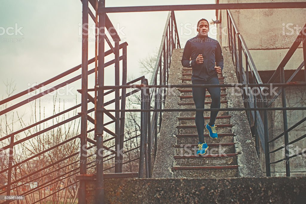 Muscular Man Running Up And Down The Stairs stock photo