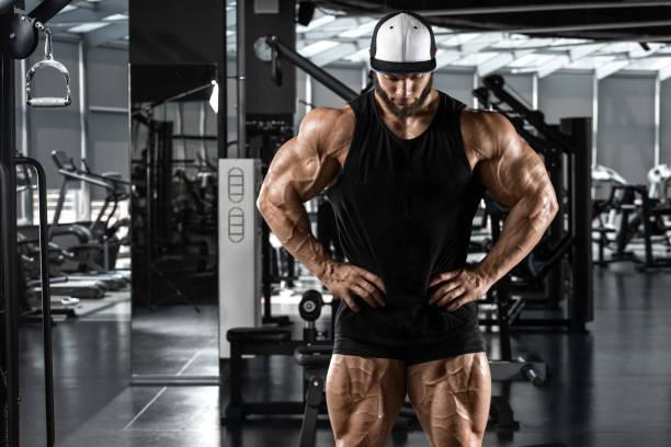 hombre musculoso mostrando músculos en el gimnasio, entrenamiento. fuerte culturismo masculino - hombres grandes musculosos fotografías e imágenes de stock
