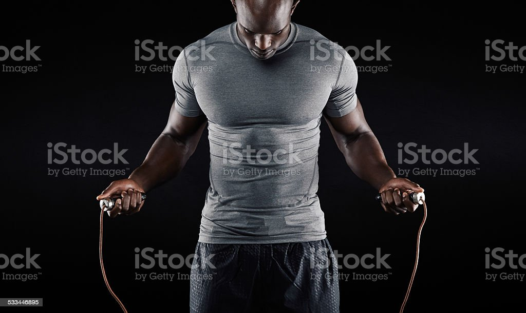 Muscular man skipping rope stock photo