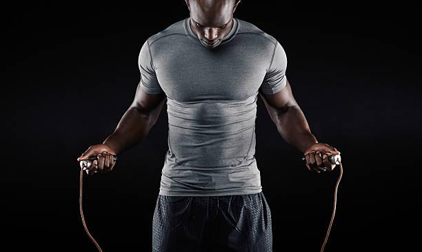 Muscular man skipping rope stock photo