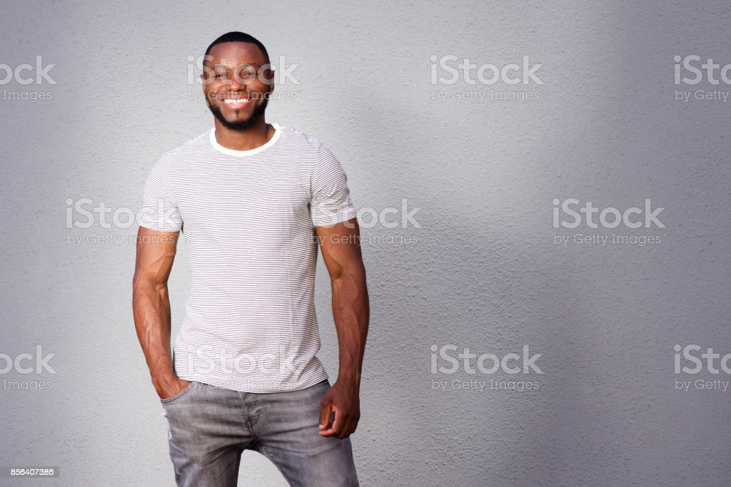 muscular man smiling and standing against gray background stock photo