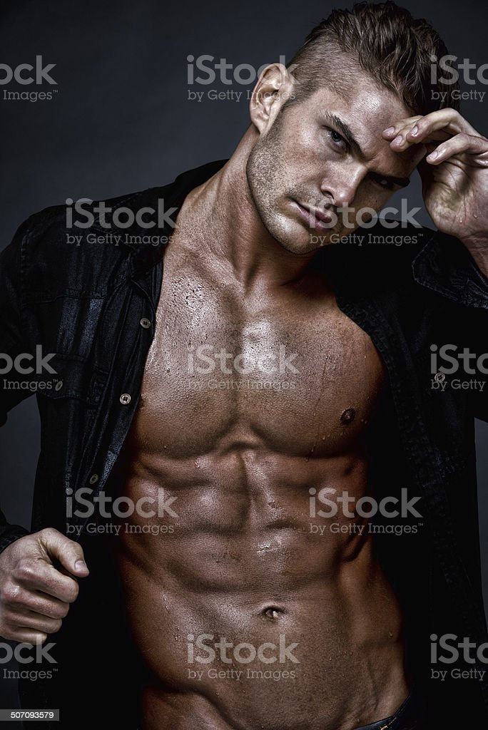 Muscular man standing in front of black background stock photo