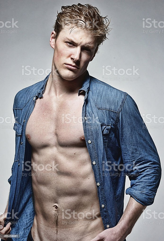 Muscular man standing with hand on shirt royalty-free stock photo
