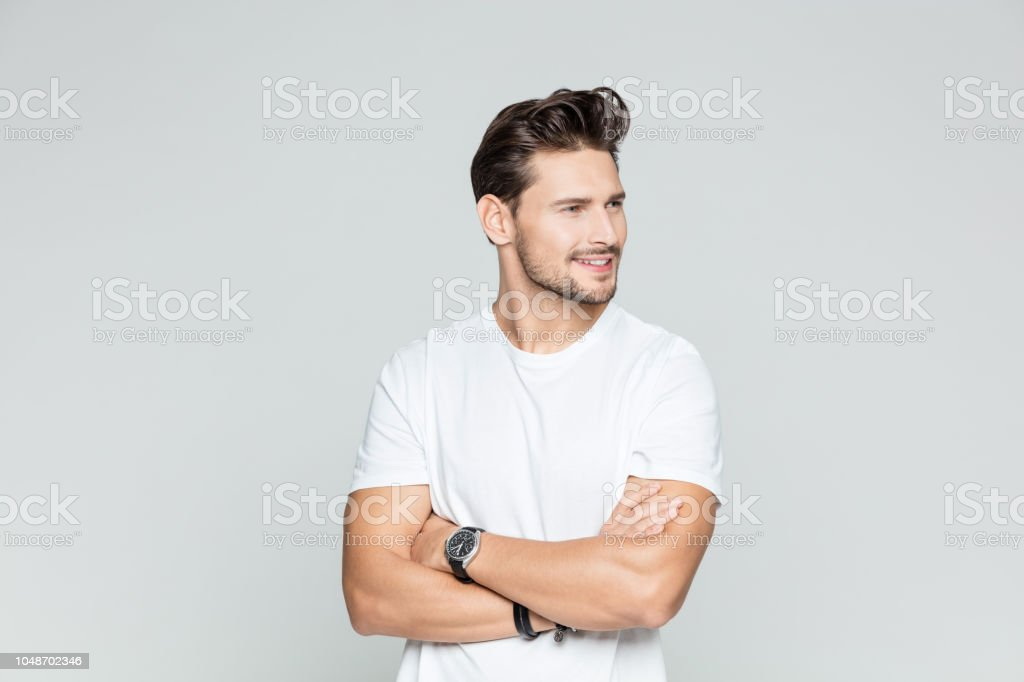 Muscular man standing with his arms crossed Portrait of muscular young man standing with his arms crossed looking away smiling on grey background. 25-29 Years Stock Photo