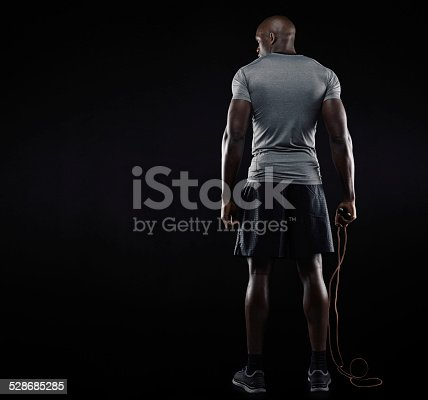 istock Muscular man standing with jumping rope 528685285
