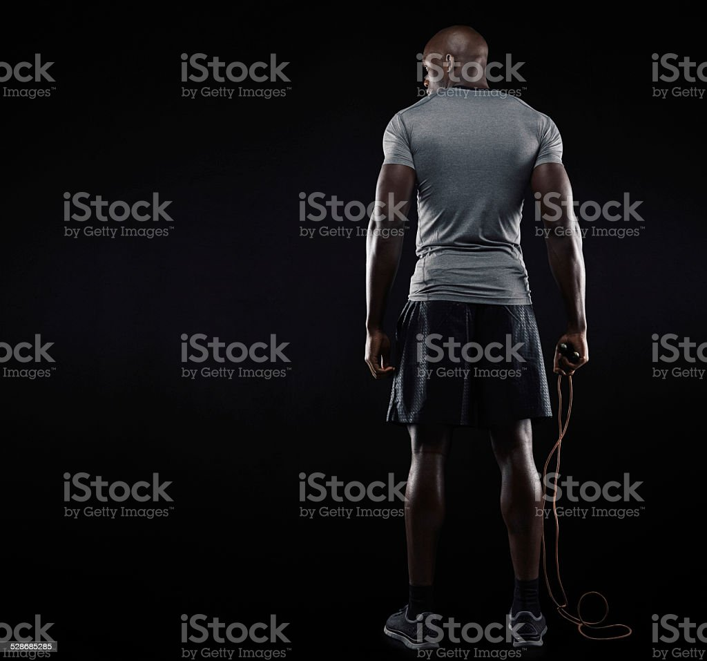 Muscular man standing with jumping rope stock photo