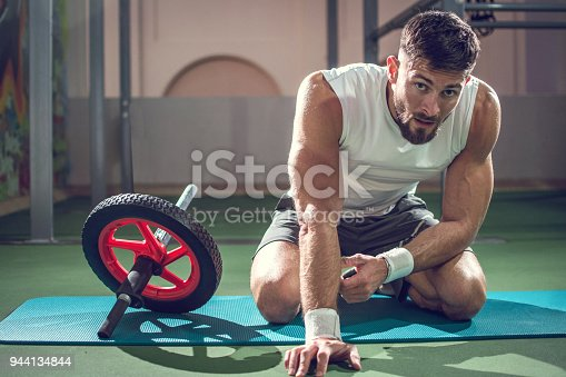 istock Muscular man taking break after training with ab wheel in gym 944134844