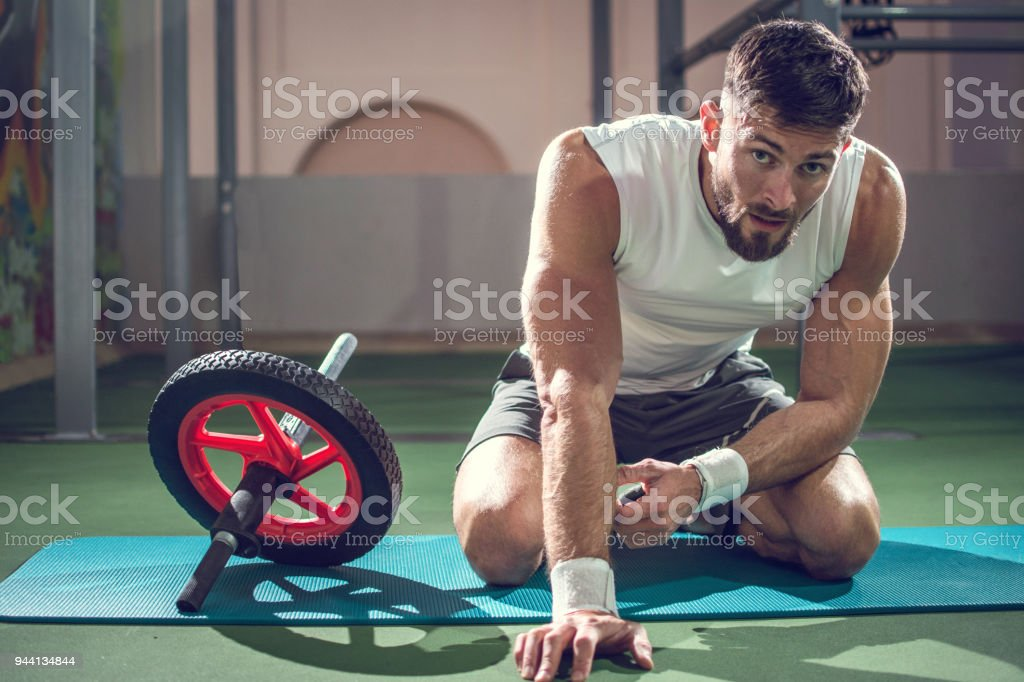 Muscular man taking break after training with ab wheel in gym stock photo